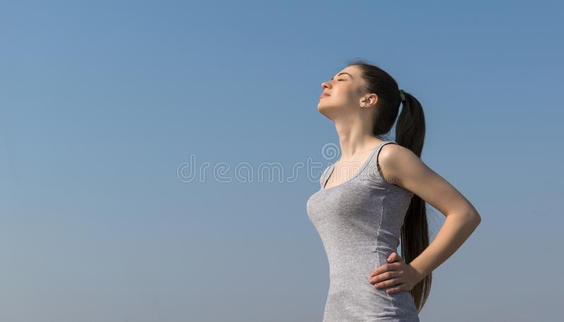 Slim beautiful girl with long hair in a gray t-shirt against the blue sky stock images