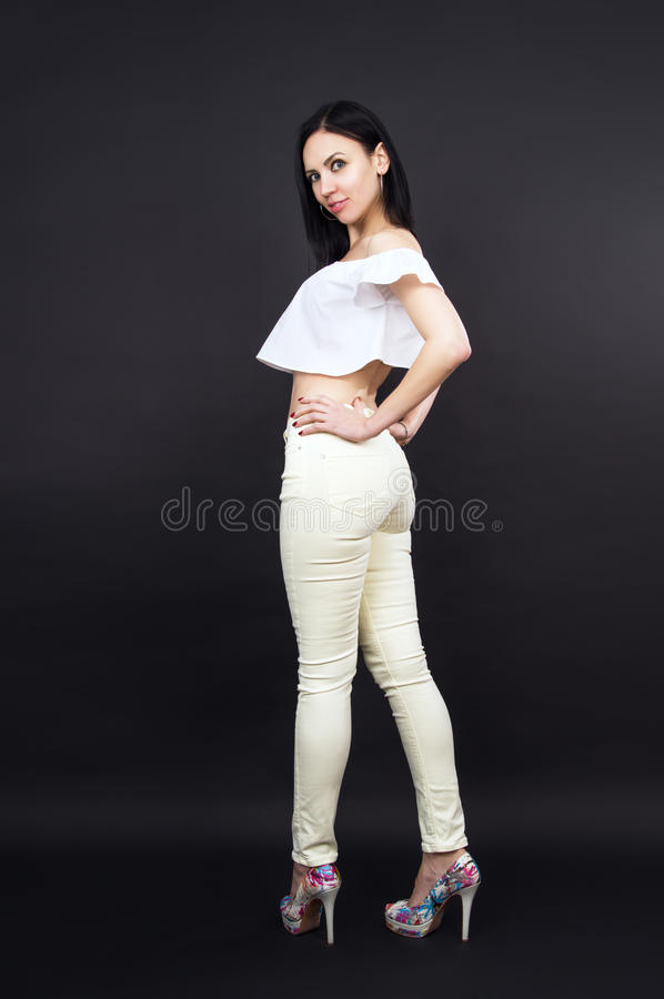 Slim beautiful girl in trousers posing on background royalty free stock photos