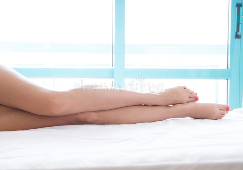Slim beautiful legs on bed. Cropped image of erotically lying on bed beautiful woman in bedroom. Crumpled white bedclothes. Slim beautiful legs on bed. Cropped royalty free stock photography