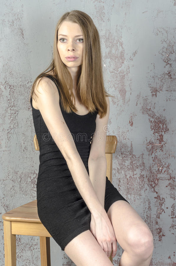 Slim beautiful red-haired girl in a black mini dress with a chair royalty free stock photo