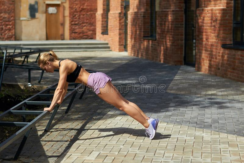 Slim blonde fitness woman doing push ups. Outdoor training. royalty free stock photo