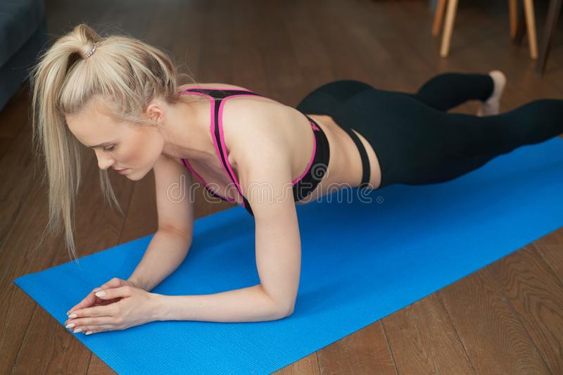 Slim blonde fitness young woman Athlete girl doing plank exercise at home on mat royalty free stock image