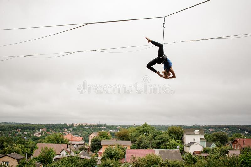 Slim blonde girl balancing high on a slackline against the grey sky and town royalty free stock photo
