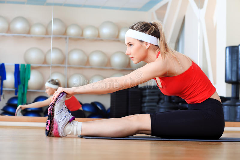 Slim body. Young sporty woman in the gym centre royalty free stock images