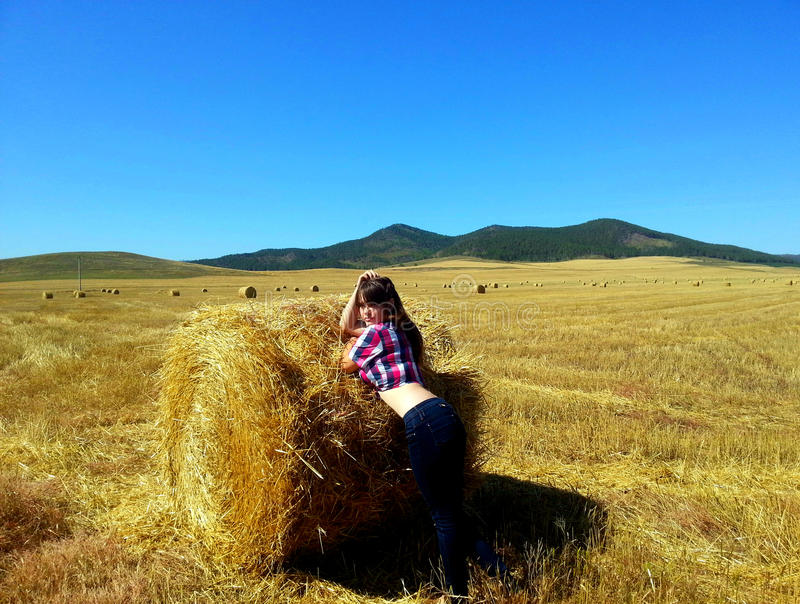 Woman posing with haystack on mowing field royalty free stock photography