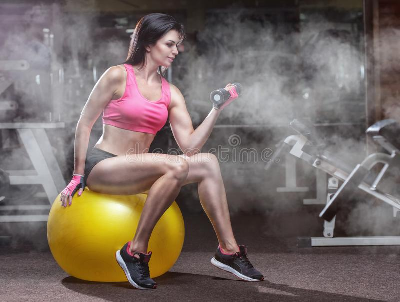 Slim, bodybuilder girl, lifts heavy dumbbell sits on a yoga ball in the gym. Sport concept, fat burning and a healthy lifestyle stock image