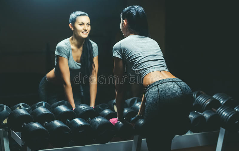 Slim, bodybuilder girl, lifts heavy dumbbell standing in front of the mirror while training in the gym. stock photo