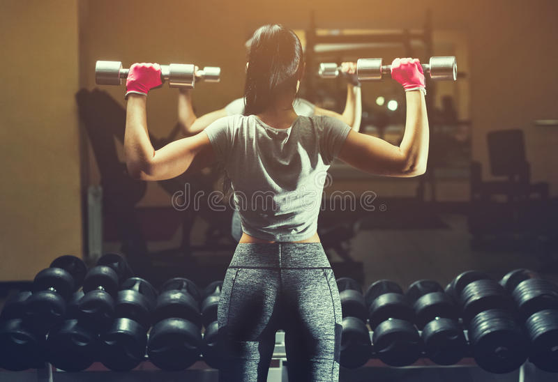 Slim bodybuilder girl lifts heavy dumbbell standing in front of the mirror while training in the gym. Sports concept fat burning and a healthy lifestyle royalty free stock photography