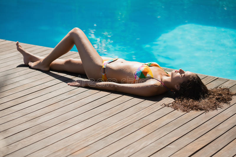 Slim brunette in bikini lying poolside stock photo