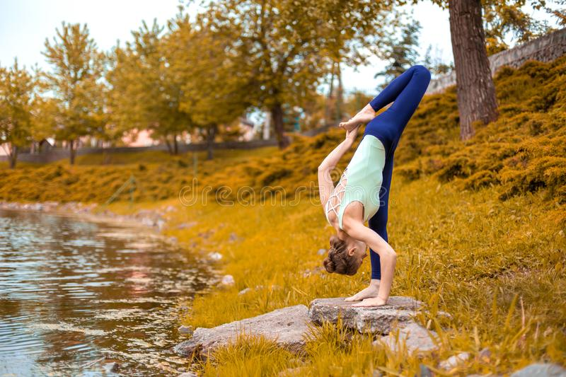 Slim brunette girl goes in for sports and performs yoga poses in the fall in nature by the lake stock photo