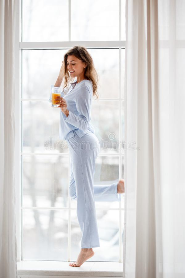 Slim brunette girl in the light-blue pajama stands on the windowsill and holds a glass of fresh juice in her hand stock image