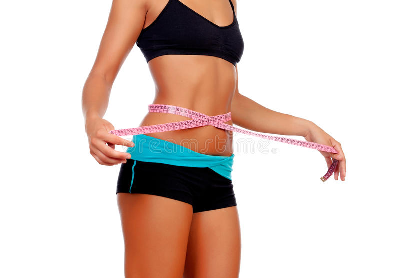 Slim brunette girl with tape measure and fitness clothes. Isolated on a white background royalty free stock images