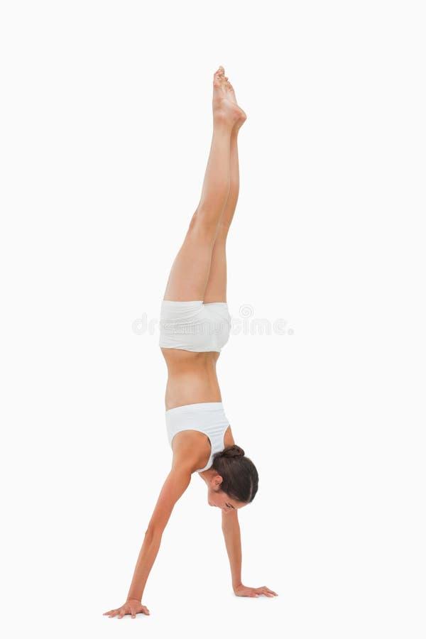 Slim brunette handstands stock photo