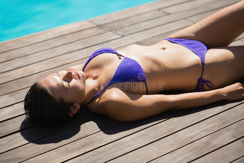 Slim brunette in purple bikini lying poolside royalty free stock image