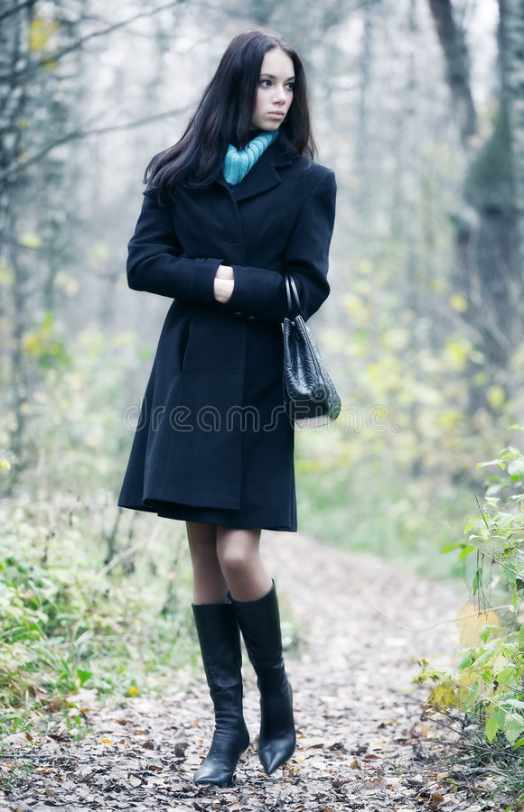 Slim brunette woman walking in a park royalty free stock image