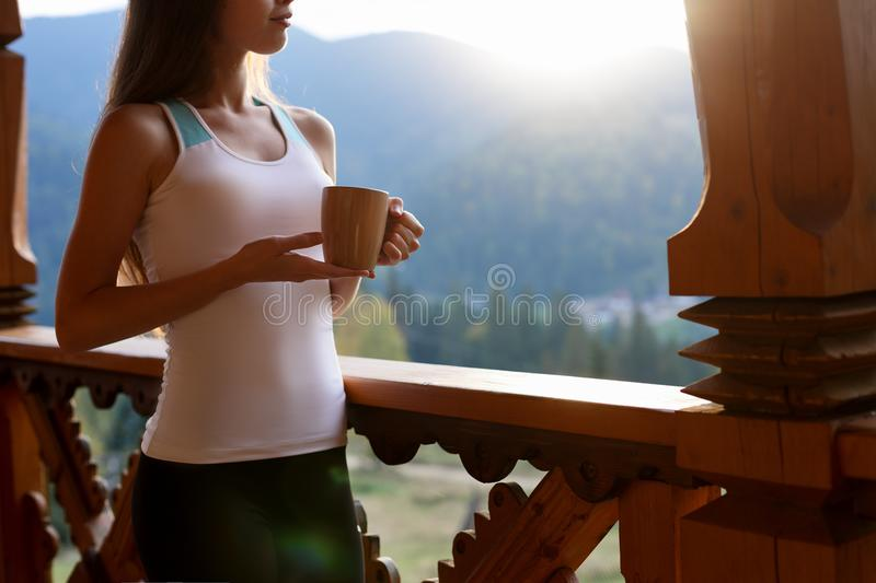 Slim caucasian woman holds cup of tea in her hands at mountain resort. Sports girl with hot coffee mug at wooden balcony royalty free stock images