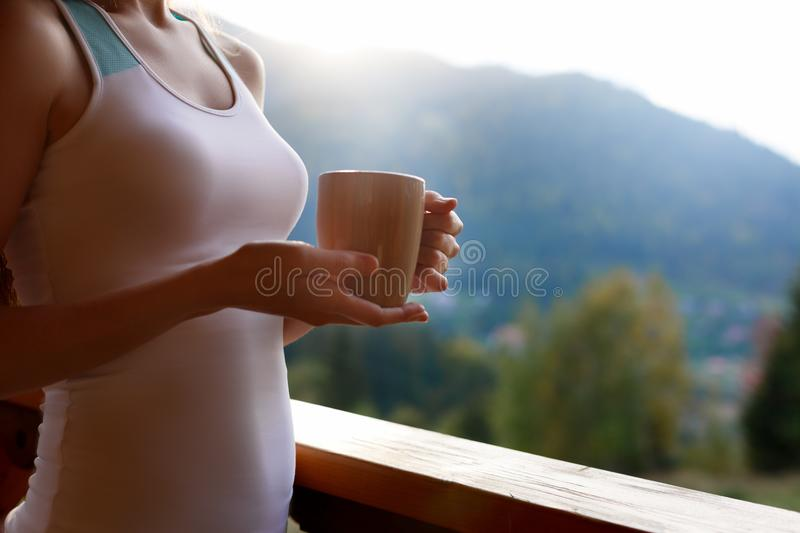Slim caucasian woman holds cup of tea in her hands at mountain resort. Sports girl with hot coffee mug at wooden balcony. Of country house. Forest and mountains royalty free stock images