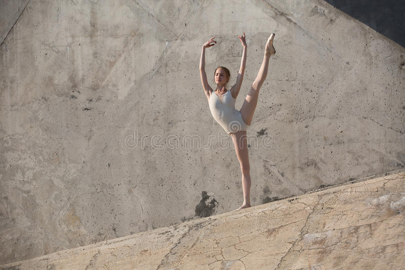Slim dancer sits in a ballet pose. Slim dancer stands in a ballet pose on a gray urban concrete background. Outdoors shooting with sun light royalty free stock image