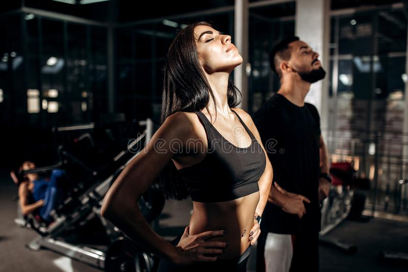 Slim dark-haired girl dressed in black sport clothes and fitness coach are doing warm up in the gym stock photos