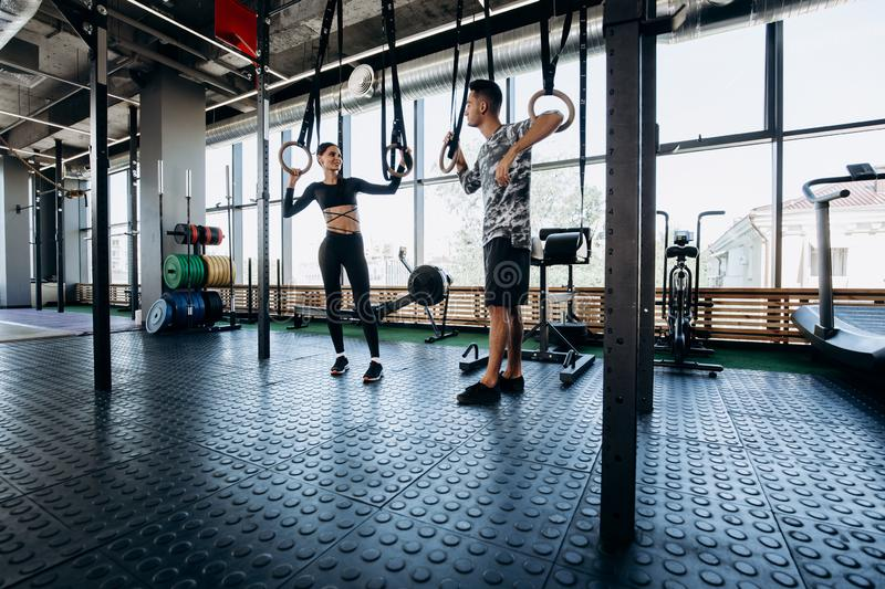 Slim dark-haired girl dressed black sports clothes and athletic man are talking in the spacious gym next to the exercise stock photo
