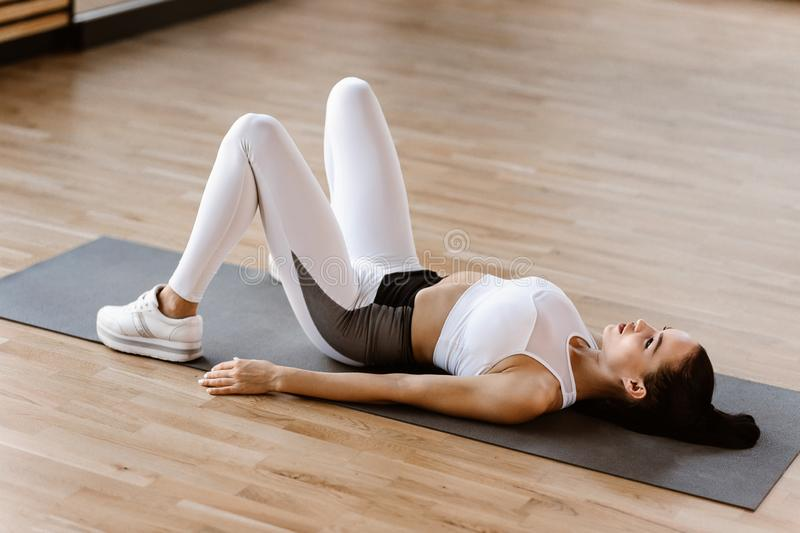 Slim dark-haired girl dressed in white sports clothes has a work out on the mat for fitness in the gym royalty free stock image