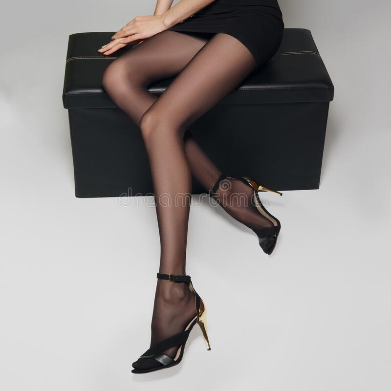 Free Slim Female Long Legs In Black Pantyhose On Leather Box Stock Photos - 191149913