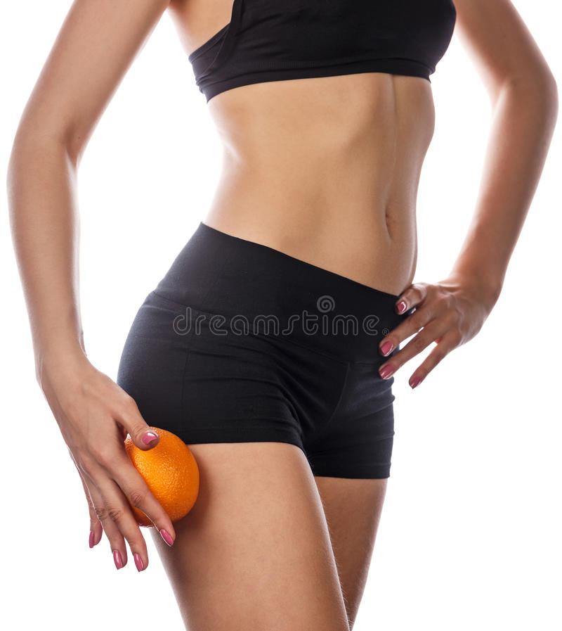 Slim figure woman holds an orange. stock image