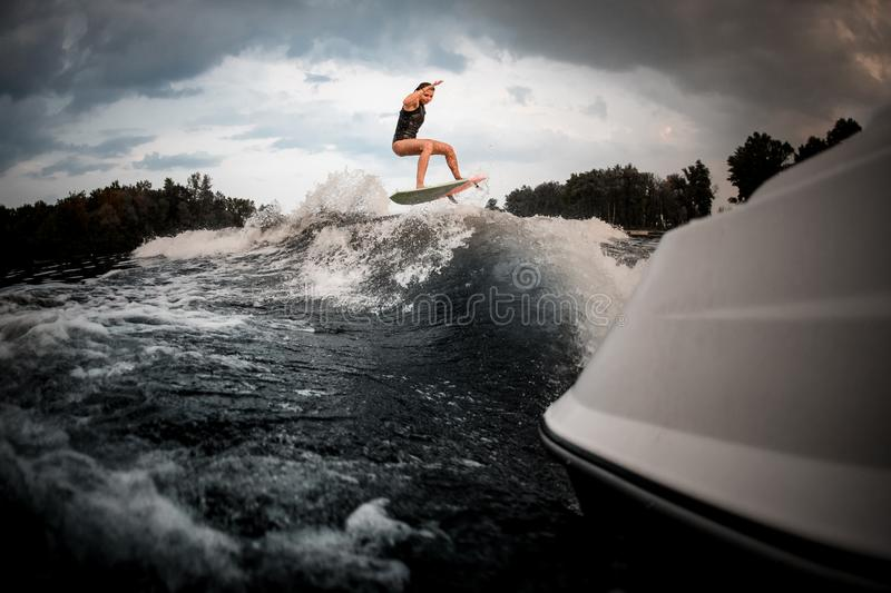 Slim fit girl jumping on the wakeboard on the river on the wave of the motorboat royalty free stock photography