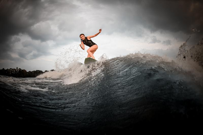 Slim fit girl riding on the wakeboard on the river in the background of trees rising hands stock images