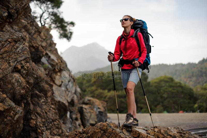 Slim fit girl in special wear standing with hiking backpack and sticks on the rock stock photos