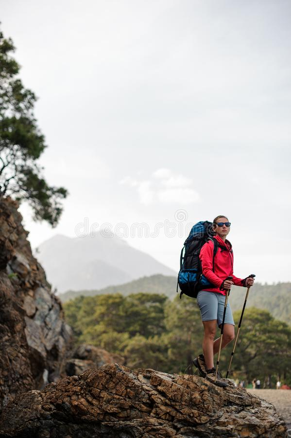 Slim fit girl in sportwear standing with hiking backpack and sticks on the rock royalty free stock photography