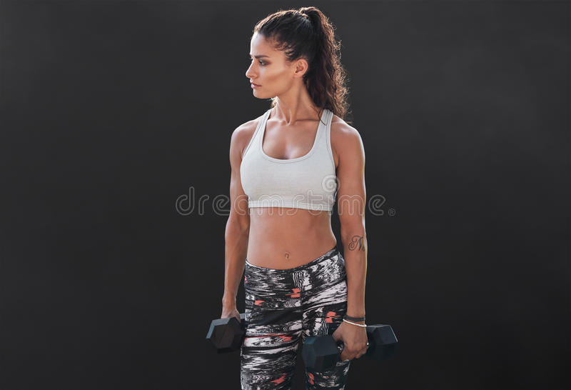 Slim and fit woman lifting hand weights. Muscular female working out with dumbbells on black background. Bodybuilding model doing fitness exercise royalty free stock photography