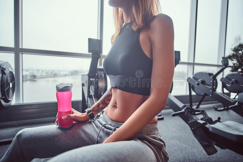 Slim fitness woman wearing sportswear resting after hard workout, holding a bottle with water. Health, diet, sport stock photo