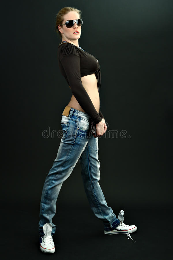 Slim girl in blue jeans with sunglasses on cyan stock images