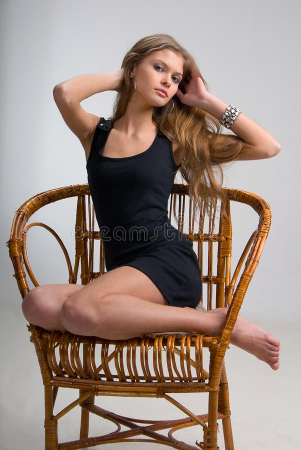 Slim girl on a chair royalty free stock image