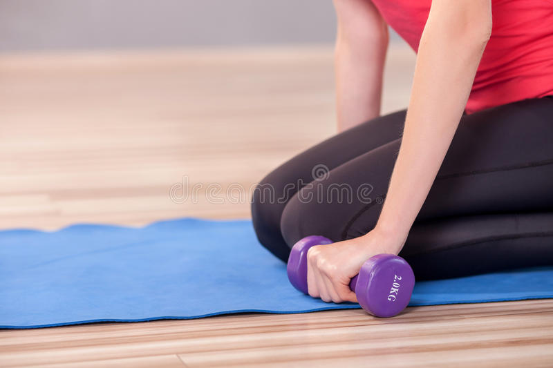 Slim girl is doing exercise in fitness center. Close up of trained body of young woman exercising in gym. She is sitting on carpet and holding dumbbell stock image