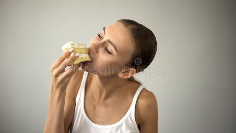 Slim girl eating cake eagerly, dieting and starving, lack of self-discipline. Stock photo royalty free stock image
