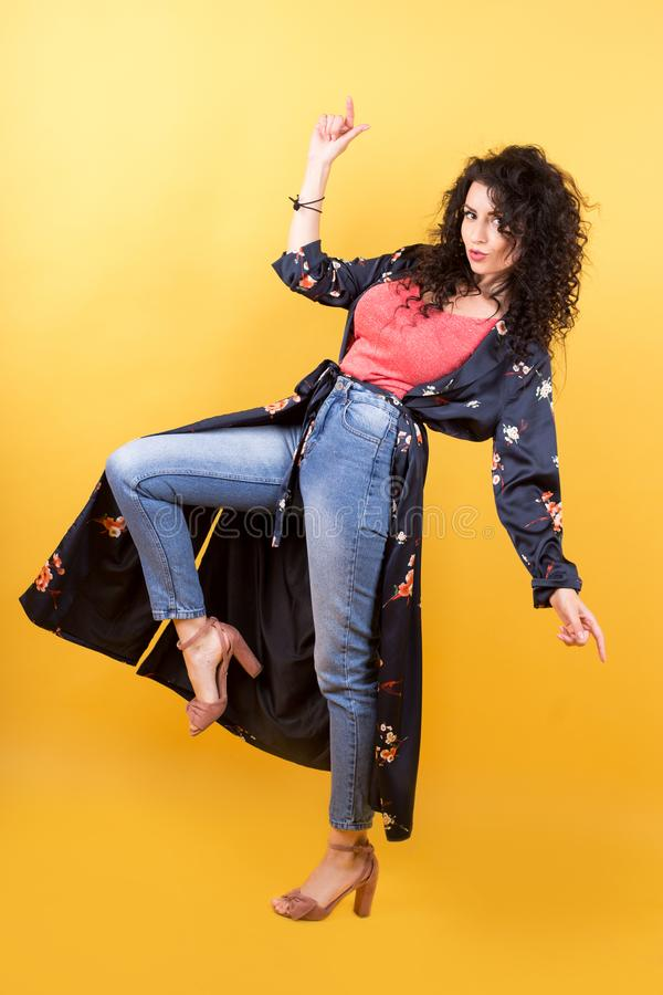 Slim girl in jeans and a lightweight full-length summer coat royalty free stock photography