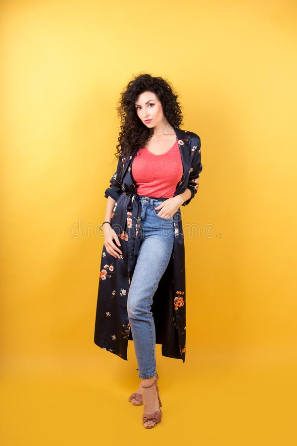 Slim girl in jeans and a lightweight full-length summer coat royalty free stock photo