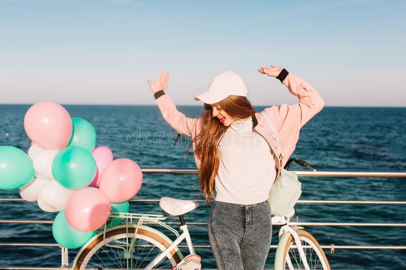 Slim girl in pink cap and sport jacket funny dancing on the sea background to celebrate her birthday. Charming young stock images