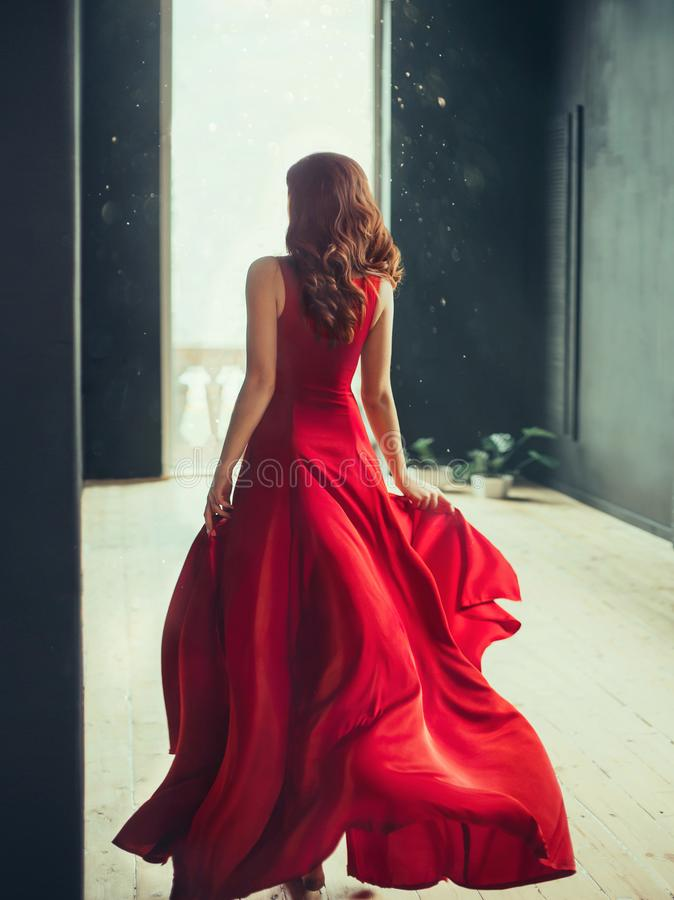 Slim girl with red hair runs into a fashionable room in a loft style with dark black walls and window to the floor stock photography