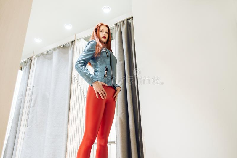 Slim girl with redheads chooses clothes. woman in red leather pants posing in fitting rooms. bottom view. Slim girl with redheads chooses clothes. woman in red royalty free stock images