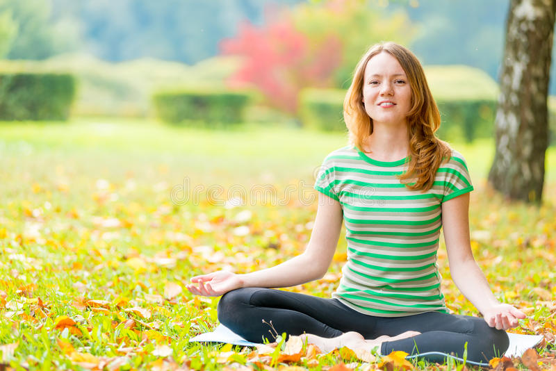 Slim girl relaxing sitting in the lotus position. Slim beautiful girl relaxing sitting in the lotus position stock images
