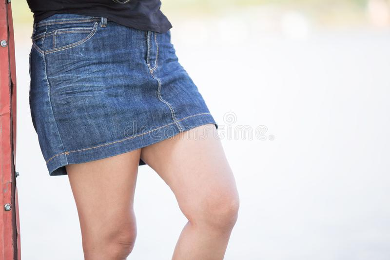 Slim girl in short denim skirt, rear view, close-up. Slender female legs on the street background, jeans fashion, hot weather stock image