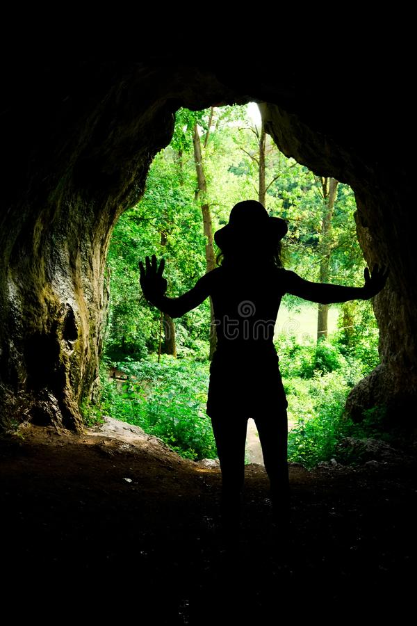 Slim girl silhouette at the entrance to natural cave in the forrest royalty free stock photo