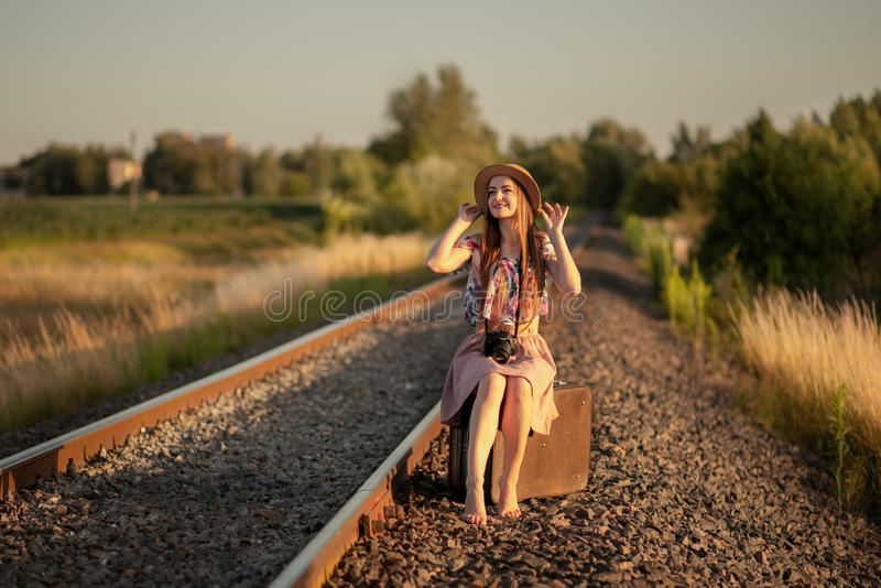 Slim girl in a straw hat sitting on suitcases on the railroad tracks, with a camera, smiling and dreaming. The concept of travel, royalty free stock photo
