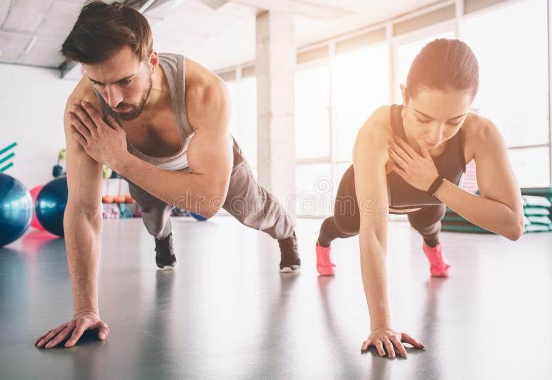Slim girl and strong man are standing in one hand plank position and balancing on that hand. They look concentrated and stock image