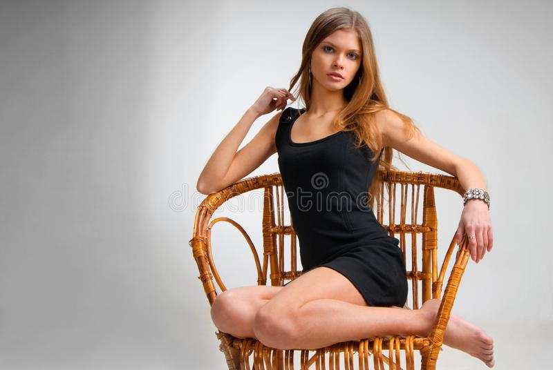 Slim girl on vintage chair stock photo