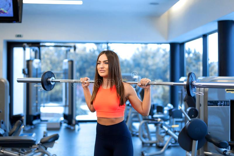 Slim handsome young woman in sportswear squats with a barbell on the shoulder in the gym royalty free stock photography