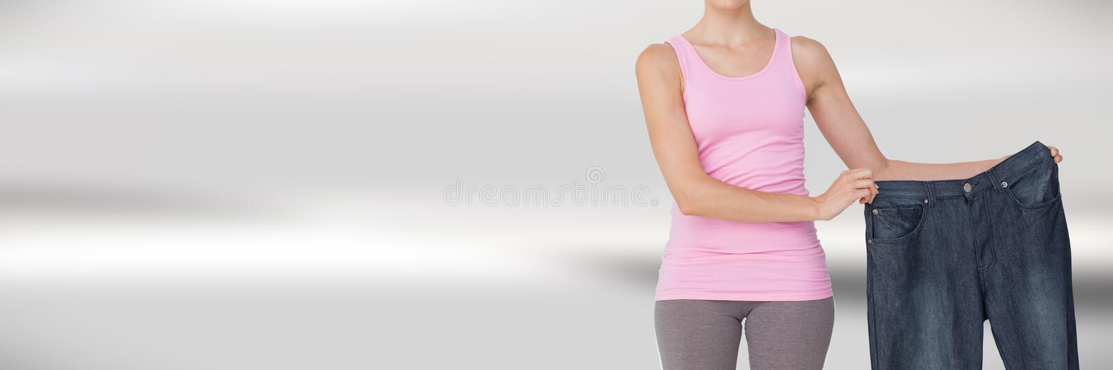 Slim healthy woman holding large trousers stock photo